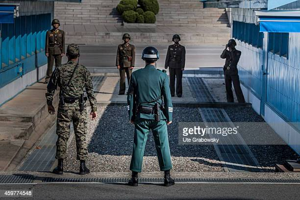 South Korean and US soldier standing at the military demarcation line separating North and South Korea within the Joint Security Area and watching...