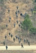 South Korean and US soldiers march on a hill during a joint live fire exercise at a military training field in Pocheon northeast of Seoul on April 11...
