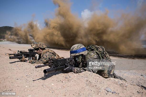 South Korean and US soldiers take a position during an annual joint military landing exercise in Pohang on South Korea's southeast coast on March 12...