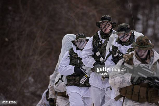 South Korean and US soldiers walk in the snow during a joint annual winter exercise in Pyeongchang some 180 kilometers east of Seoul on January 28...