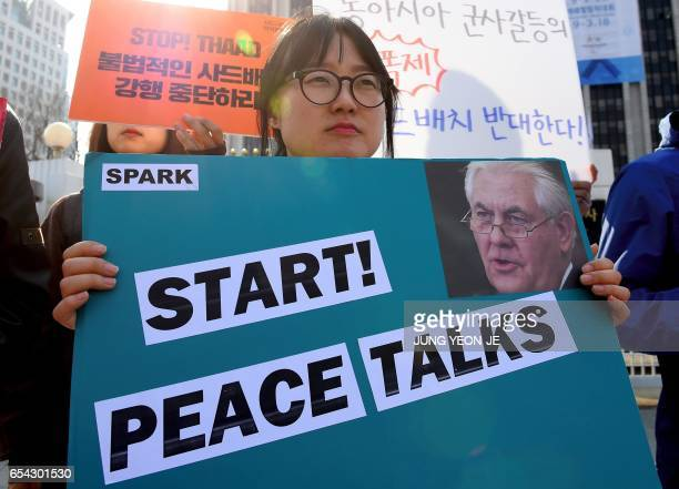 A South Korean antiwar activist holds a placard showing a portrait of US Secretary of State Rex Tillerson during a rally against the planned...
