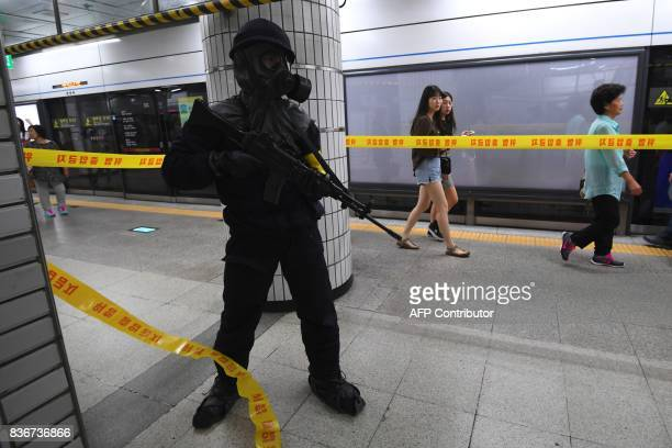 South Korean armed policeman takes part in an antiterror drill at a subway station in Seoul on August 22 on the sidelines of a South KoreaUS joint...