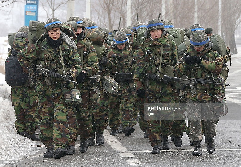 South Korean armed soldiers march during a military field exercise in Paju near the demilitarized zone dividing the two Koreas on February 12, 2013. North Korea on February 12 staged its most powerful nuclear test yet, claiming a breakthrough with a 'miniaturised' device in a striking act of defiance that drew condemnation from global powers including its sole patron China. REPUBLIC