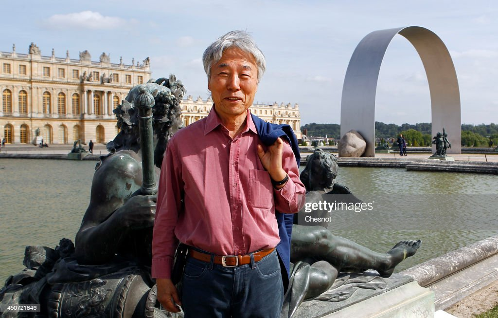 South Korean artist <a gi-track='captionPersonalityLinkClicked' href=/galleries/search?phrase=Lee+Ufan&family=editorial&specificpeople=8945134 ng-click='$event.stopPropagation()'>Lee Ufan</a> poses beside one of his artworks entitled 'L'arche de Versailles' ('The arch of Versailles') during the exhibition '<a gi-track='captionPersonalityLinkClicked' href=/galleries/search?phrase=Lee+Ufan&family=editorial&specificpeople=8945134 ng-click='$event.stopPropagation()'>Lee Ufan</a> Versailles' at the Chateau de Versailles on June 16, 2014 in Versailles, France. Painter and sculptor <a gi-track='captionPersonalityLinkClicked' href=/galleries/search?phrase=Lee+Ufan&family=editorial&specificpeople=8945134 ng-click='$event.stopPropagation()'>Lee Ufan</a>, 77, has created a variety of artworks made of stone and steel for an exhibition at the Chateau de Versailles, outside Paris. The exhibition opens from June 17 until November 02, 2014 at the Chateau de Versailles.