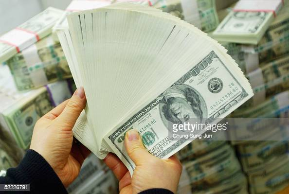 South Korean banker carries US dollar bank notes at the Korea Exchange bank on February 22 2005 in Seoul South Korea The South Korean won jumped to...