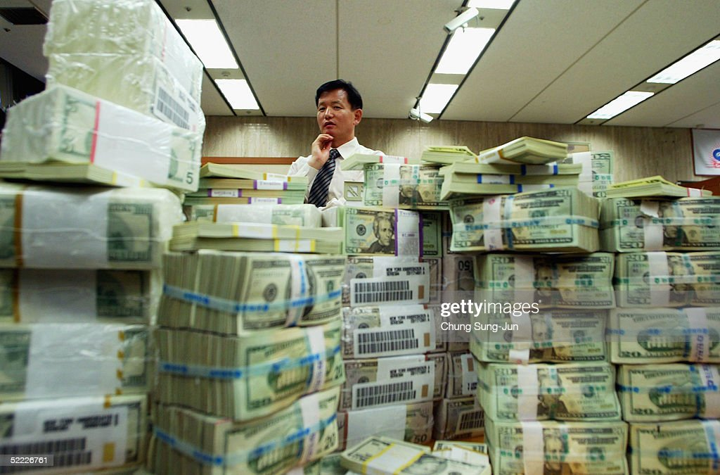 A South Korean banker stands behind US dollar bank notes at the Korea Exchange bank on February 22, 2005 in Seoul, South Korea. The South Korean won jumped to its highest intraday level in more than seven years in domestic trade on Tuesday, boosted by strong foreign equity buying and exporter deals.