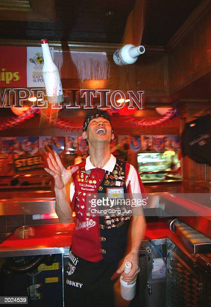 South Korean bartender juggle bottles while making a drink during a bartender contest May 23 2003 in Seoul South Korea The winner will compete in the...