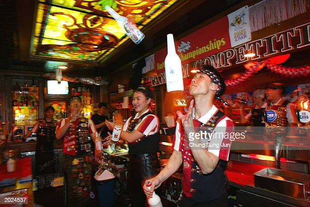 South Korean bartenders juggle bottles while making a drink during a bartender contest May 23 2003 in Seoul South Korea The winner will compete in...