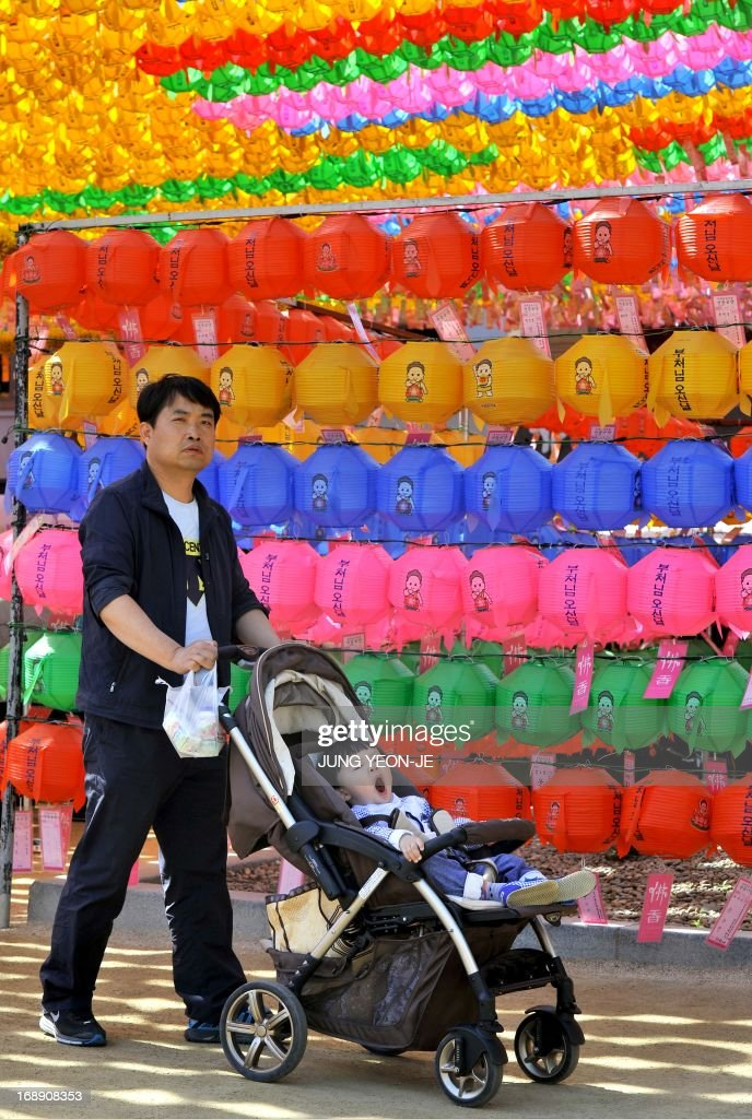 A South Korean boy in a pram yawns in front of rows of lotus lanterns during a ceremony to celebrate the birthday of Buddha at Jogye temple in Seoul on May 17, 2013. Buddhism is one of South Korea's largest and most active religions with millions of followers. Although the exact date is unknown, Buddha's official birthday is celebrated on April 8th of the lunar calendar in South Korea. AFP PHOTO / JUNG YEON-JE
