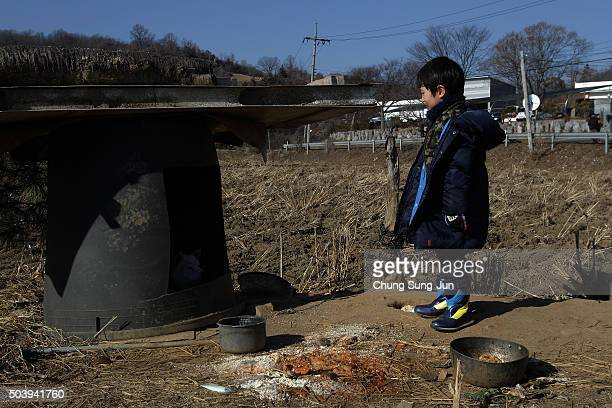 South Korean boy looks at a dog near the site of loudspeakers placed near the Demilitarized zone separating South and North Korea on January 8 2016...