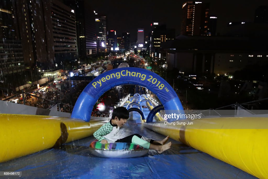 A South Korean boy slides down on an inflatable ring during the 'Bobsleigh In the City' on August 19, 2017 in Seoul, South Korea. The 22-metre-high 300-metre-long water slider has been set up in the central Seoul to promote upcoming PyeongChang Winter Olympics.