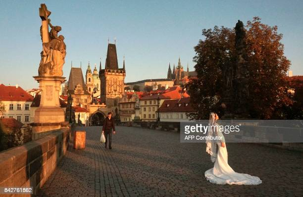 A South Korean bride poses for a photographer on the landmark Charles Bridge early morning on September 05 in Prague / AFP PHOTO / Michal Cizek