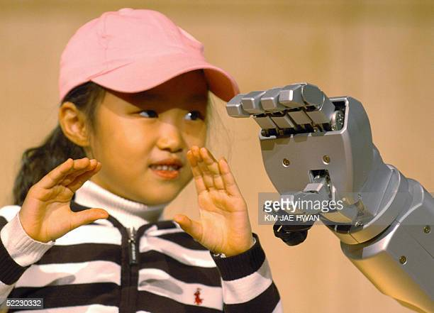 South Korean child tries to communicate with newly unveil humanoid Robot 'HUBO' by hand signals at Korea Advanced Institute of Science and Technology...