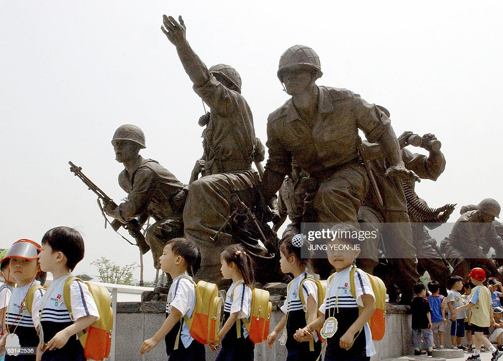 South Korean children march past a brozne statue of soldiers at the Korean war Memorial in Seoul 24 June 2005 South Korea has invited 83 foreign...