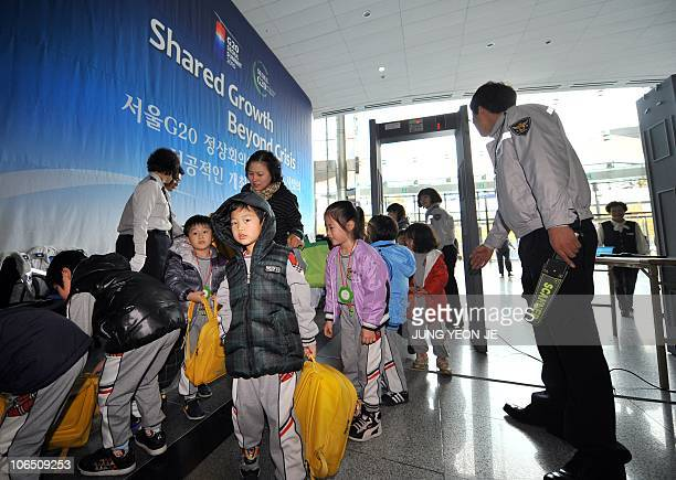 South Korean children pass through a security check as police officers inspect visitors for the upcoming G20 Summit at its venue in Seoul on November...