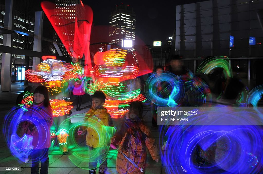 South Korean children play with colourful light sticks for a light show organised by the Everland amusement park in central Seoul on February 21, 2013. The show came ahead of the first full-moon day on the Lunar Year calendar, which falls on February 24. South Korean have tradionally observed the day with firework or wielded portable bonfires in cans. AFP PHOTO / KIM JAE-HWAN