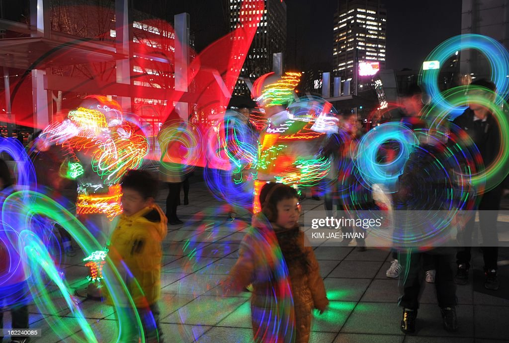 South Korean children play with colourful light sticks for a light show organised by the Everland amusement park in central Seoul on February 21, 2013. The show came ahead of the first full-moon day on the Lunar Year calendar, which falls on February 24. South Korean have tradionally observed the day with firework or wielded portable bonfires in cans.