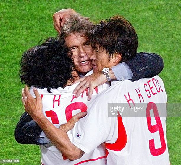 REPUBLIC OF KOREA DAEJEON South Korean coach Guus Hiddink C hugs midfielder Ahn Junghwan L and forward Seol Kihyeon R after their win over Italy in...