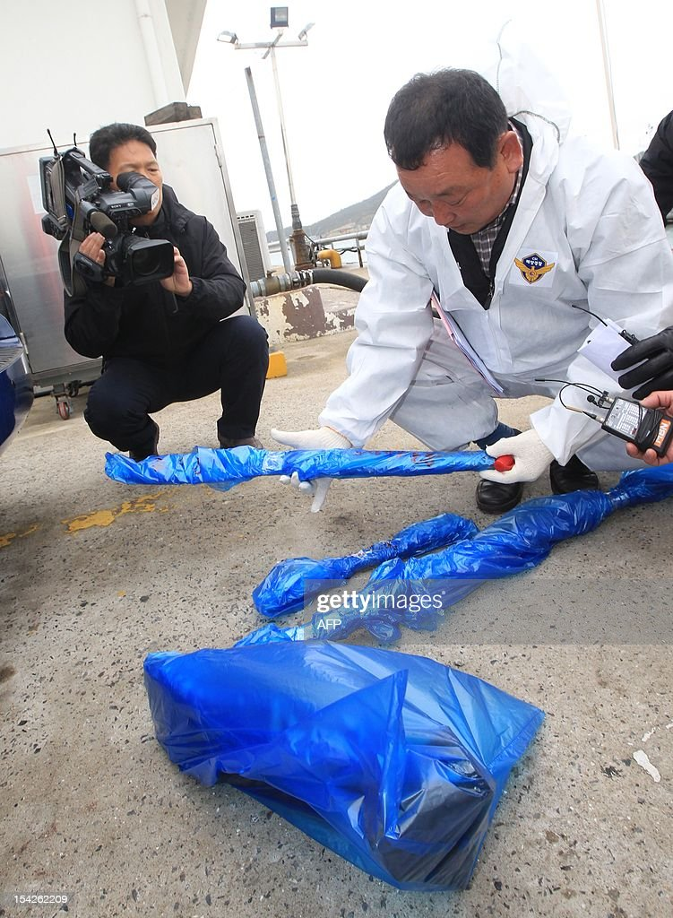 South Korean coastguard investigators checks weapons after a Chinese fishing boat arrived in the southwestern port of Mokpo on October 17, 2012, a day after it was seized for illegal fishing in the Yellow Sea. South Korea's coastguard said on October 17 it was holding 23 Chinese fishermen in custody for questioning after a violent clash in the Yellow Sea that left one Chinese crew member dead. REPUBLIC OF KOREA OUT AFP PHOTO/DONG-A ILBO