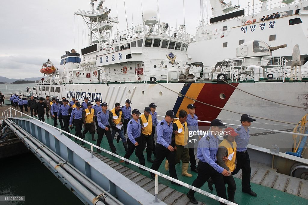 South Korean coastguard officers escort Chinese sailors after their boat arrived in the southwestern port of Mokpo on October 17, 2012, a day after it was seized for illegal fishing in the Yellow Sea. South Korea's coastguard said on October 17 it was holding 23 Chinese fishermen in custody for questioning after a violent clash in the Yellow Sea that left one Chinese crew member dead. REPUBLIC OF KOREA OUT AFP PHOTO/DONG-A ILBO