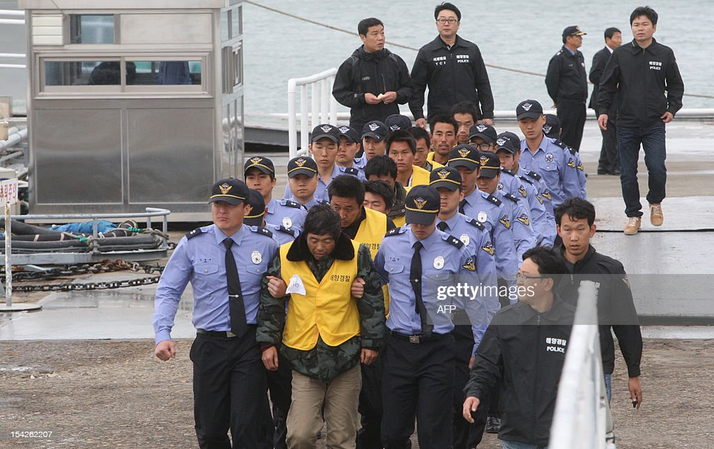 South Korean coastguard officers escort Chinese sailors after their boat arrived in the southwestern port of Mokpo on October 17, 2012, a day after it was seized for illegal fishing in the Yellow Sea. South Korea's coastguard said on October 17 it was holding 23 Chinese fishermen in custody for questioning after a violent clash in the Yellow Sea that left one Chinese crew member dead. REPUBLIC