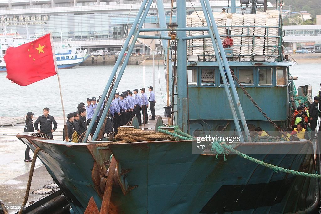 South Korean coastguard officers stand on guard after a Chinese fishing boat arrived in the southwestern port of Mokpo on October 17 a day after it...