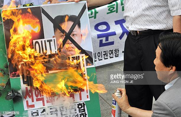 A South Korean conservative activist burns a placard showing a portrait of North Korean leader Kim JongUn during an antiPyongyang rally in Seoul on...