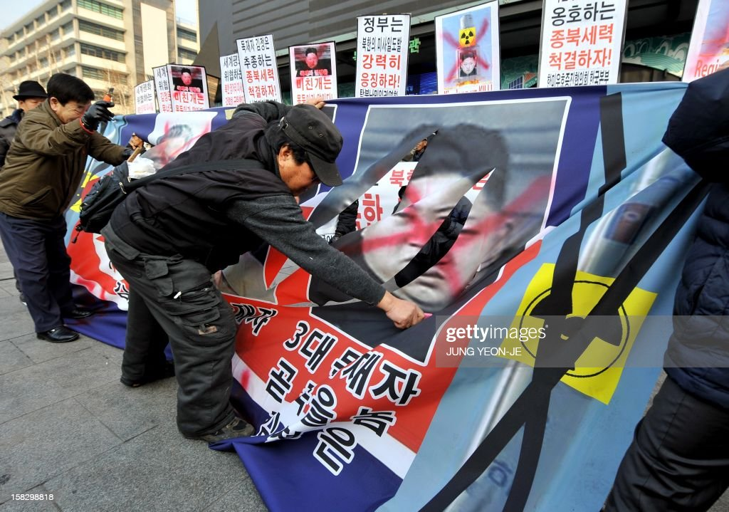 A South Korean conservative activist cuts off a portrait of North Korean leader Kim Jong-Un from a banner (C) during a protest denouncing North Korea's rocket launch the day before, in Seoul on December 13, 2012. North Korea's rocket launch is a timely boost for its young leader, securing his year-old grip on power and laying to rest the humiliation of a much-hyped but failed launch eight months ago, analysts say. AFP PHOTO / JUNG YEON-JE