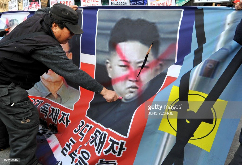 A South Korean conservative activist cuts through a portrait of North Korean leader Kim Jong-Un on a banner (C) during a protest denouncing North Korea's rocket launch the day before, in Seoul on December 13, 2012. North Korea's rocket launch is a timely boost for its young leader, securing his year-old grip on power and laying to rest the humiliation of a much-hyped but failed launch eight months ago, analysts say. AFP PHOTO / JUNG YEON-JE