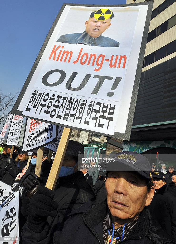 A South Korean conservative activist displays a placard showing North Korean leader Kim Jong-Un during a rally denouncing North Korea's nuclear test, in Seoul on February 13, 2013. South Korea said on February 13 it would accelerate the development of longer-range ballistic missiles that could cover the whole of North Korea in response to a third nuclear test by Pyongyang.