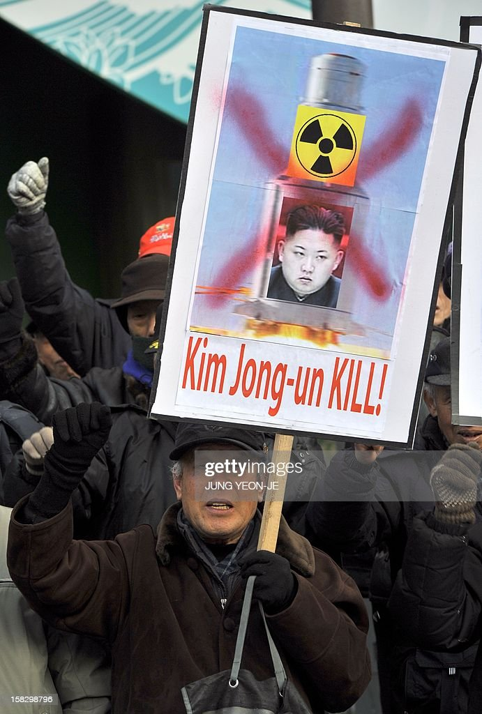 A South Korean conservative activist shouts slogans as he holds a placard showing a portrait of North Korean leader Kim Jong-Un during a protest denouncing North Korea's rocket launch the day before, in Seoul on December 13, 2012. North Korea's rocket launch is a timely boost for its young leader, securing his year-old grip on power and laying to rest the humiliation of a much-hyped but failed launch eight months ago, analysts say.