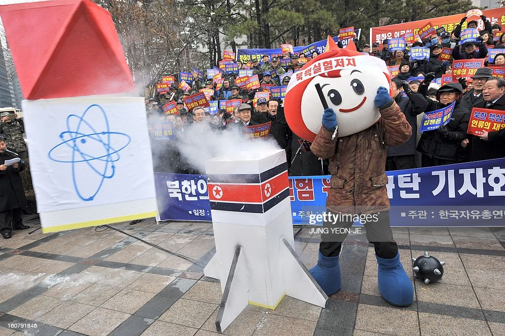 A South Korean conservative activist smashes a mock North Korean nuclear missile during a protest against North Korea's threat of its nuclear test, in Seoul on February 6, 2013. North Korea warned on February 5 of making a move 'beyond imagination,' as the communist state ramps up daily threats of an apparently imminent nuclear test. The banner reads 'A rally denouncing the threat of the 3rd nuclear test by North Korea'. AFP PHOTO / JUNG YEON-JE