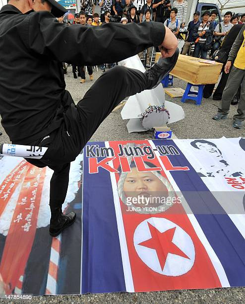 A South Korean conservative activist treads on a banner displaying a portrait of North Korean current leader Kim JongUn superimposed on top of a...