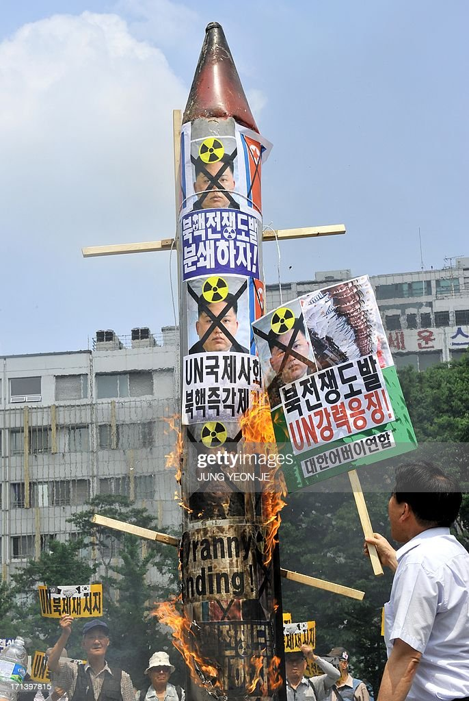 South Korean conservative activists burn a mock missile (C) showing portraits of North Korean leader Kim Jong-Un during an anti-Pyongyang rally to mark the 63th anniversary of the Korean War and denounce North Korea's nuclear programs, in Seoul on June 24, 2013. The Korean peninsula is the world's last Cold War frontier as Stalinst North Korea and pro-Western South Korea have been technically at war since the 1950-53 conflict.