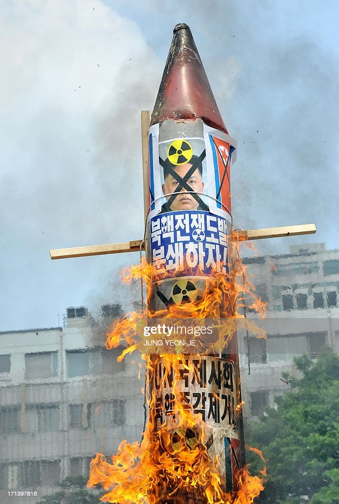 South Korean conservative activists burn a mock missile showing portrait of North Korean leader Kim Jong-Un during an anti-Pyongyang rally to mark the 63th anniversary of the Korean War and denouncing North Korea's nuclear programs, in Seoul on June 24, 2013. The Korean peninsula is the world's last Cold War frontier as Stalinst North Korea and pro-Western South Korea have been technically at war since the 1950-53 conflict.
