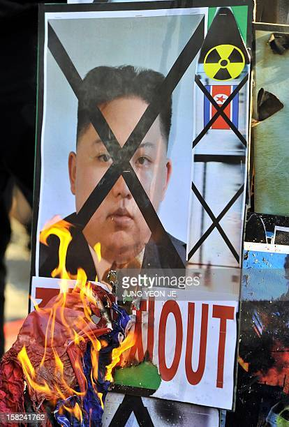 South Korean conservative activists burn a placard showing a portrait of North Korean leader Kim JongUn during a protest denouncing North Korea's...