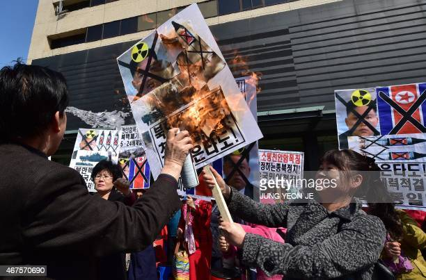 South Korean conservative activists burn a portrait of North Korean leader Kim JongUn during an antiNorth Korea rally to mark the 5th anniversary of...