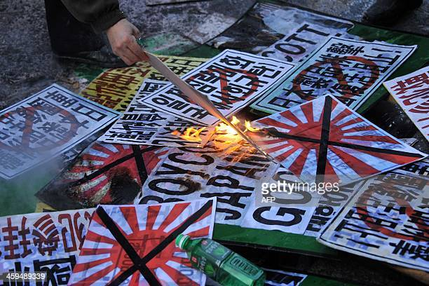 South Korean conservative activists burn placards during a protest to lodge a complaint against Japanese Prime Minister Shinzo Abe visiting the...