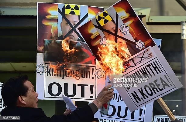 South Korean conservative activists burn placards showing portraits of North Korean leader Kim JongUn during a rally denouncing North Korea's...
