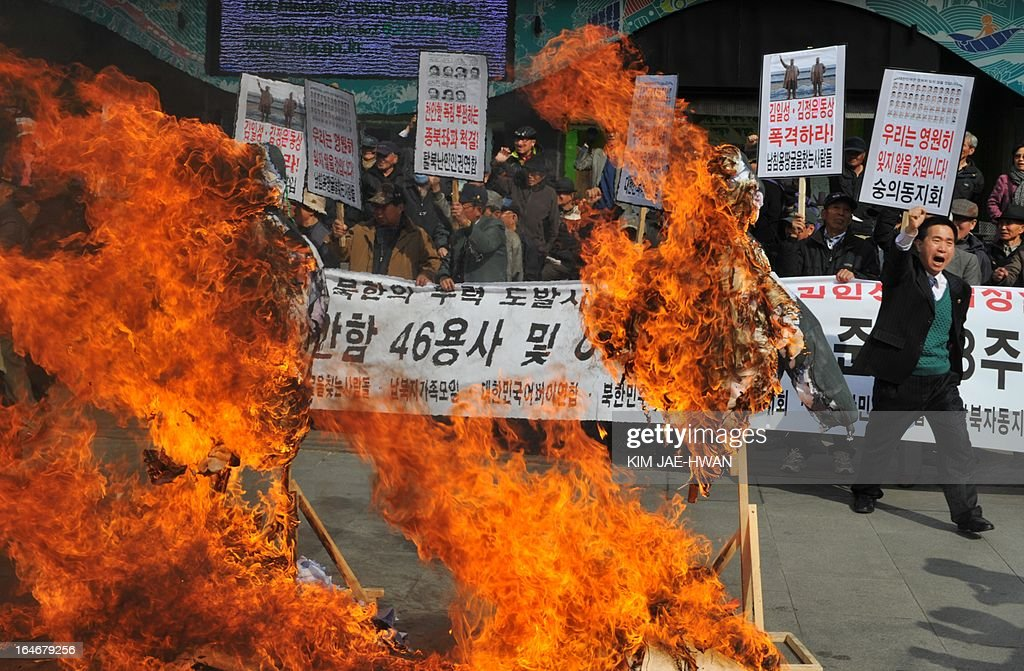 South Korean conservative activists burn the effigies of North Korea's late president Kim Il-Sung and his late son Kim Jong-Il during a rally in Seoul on March 26, 2013, to mark the third anniversary of the 2010 sinking of the naval vessel 'Cheonan' claiming the lives of 46 sailors. North Korea's military put its 'strategic' rocket units on a war footing on March 26, with a fresh threat to strike targets on the US mainland, Hawaii and Guam, as well as South Korea. HWAN