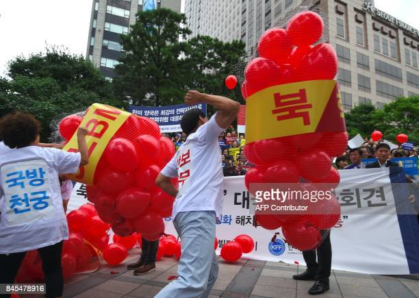 South Korean conservative activists burst balloons with yellow banners reading 'ICBM' and 'SLBM' the respective acronyms for intercontinental...