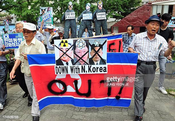 South Korean conservative activists carry a North Korean flag and portraits of North Korea's founder Kim IlSung late leader Kim JongIl and present...