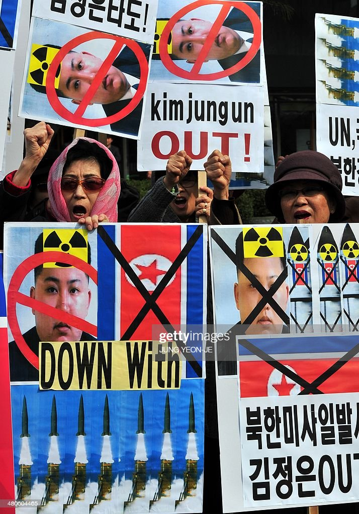 South Korean conservative activists chant slogans with placards showing portrait of North Korean leader Kim Jong-Un during a rally denouncing North Korea's missile test-launch in Seoul on March 26, 2014. North Korea test-fired two medium-range ballistic missiles on March 26, prompting a stern US reaction after President Barack Obama hosted a landmark Japan-South Korea summit aimed at uniting the three nations against Pyongyang's nuclear threat.