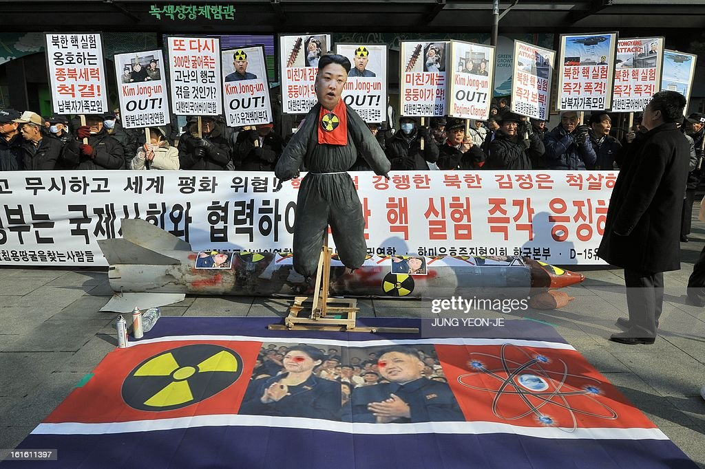 South Korean conservative activists display placards behind an effigy of North Korean leader Kim Jong-Un (C) during a rally denouncing North Korea's nuclear test, in Seoul on February 13, 2013. South Korea said on February 13 it would accelerate the development of longer-range ballistic missiles that could cover the whole of North Korea in response to a third nuclear test by Pyongyang. AFP PHOTO / JUNG YEON-JE