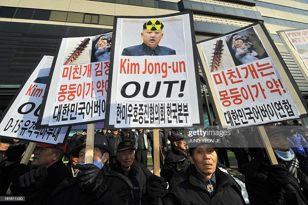 South Korean conservative activists display placards showing North Korean leader Kim Jong-Un during a rally denouncing North Korea's nuclear test, in Seoul on February 13, 2013. South Korea said on February 13 it would accelerate the development of longer-range ballistic missiles that could cover the whole of North Korea in response to a third nuclear test by Pyongyang. AFP PHOTO / JUNG YEON-JE