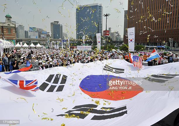 South Korean conservative activists from the Korea Freedom Federation display a huge national flag during a ceremony marking the 63rd anniversary of...