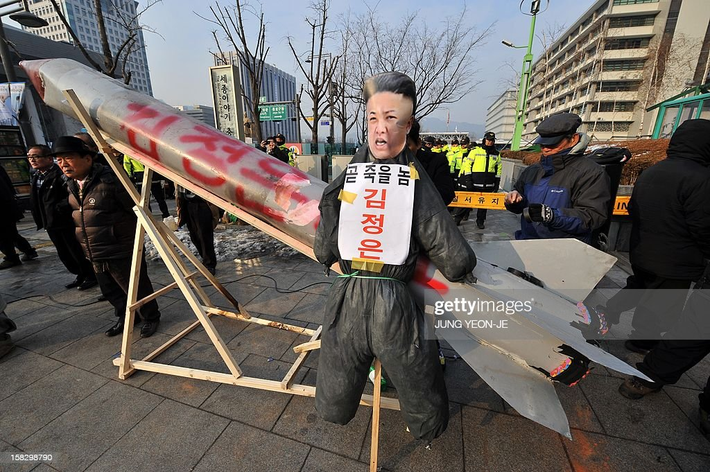 South Korean conservative activists hang an effigy (C) of North Korean leader Kim Jong-Un on a mock North Korean missile during a protest denouncing North Korea's rocket launch the day before, in Seoul on December 13, 2012. North Korea's rocket launch is a timely boost for its young leader, securing his year-old grip on power and laying to rest the humiliation of a much-hyped but failed launch eight months ago, analysts say. AFP PHOTO / JUNG YEON-JE