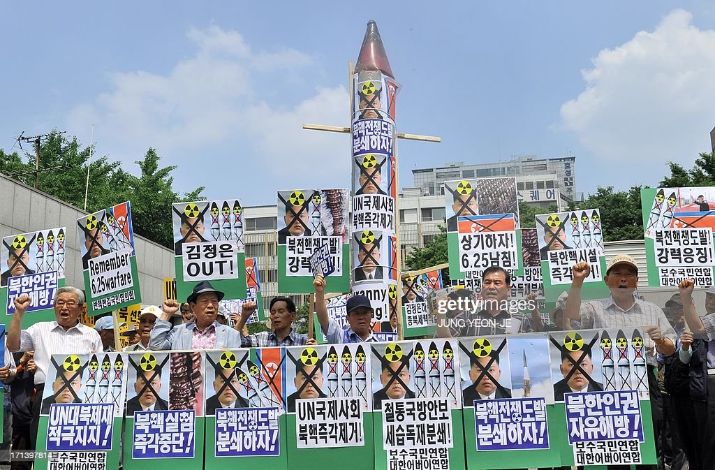 South Korean conservative activists hold a mock missile (C) and placards showing portrait of North Korean leader Kim Jong-Un during an anti-Pyongyang rally to mark the 63th anniversary of the Korean War and denouncing North Korea's nuclear programs, in Seoul on June 24, 2013. The Korean peninsula is the world's last Cold War frontier as Stalinst North Korea and pro-Western South Korea have been technically at war since the 1950-53 conflict.