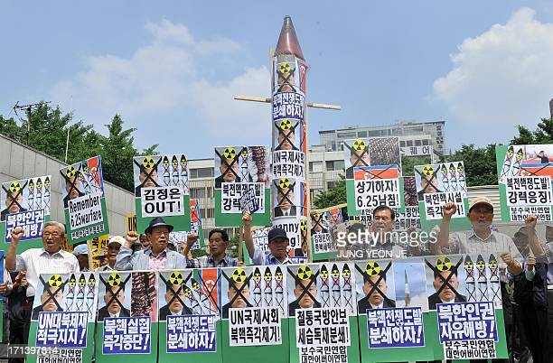 South Korean conservative activists hold a mock missile and placards showing portrait of North Korean leader Kim JongUn during an antiPyongyang rally...
