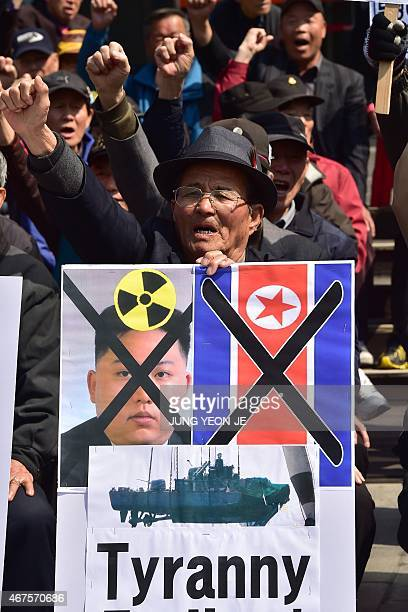 South Korean conservative activists hold a placard showing a portrait of North Korean leader Kim JongUn during an antiNorth Korea rally to mark the...